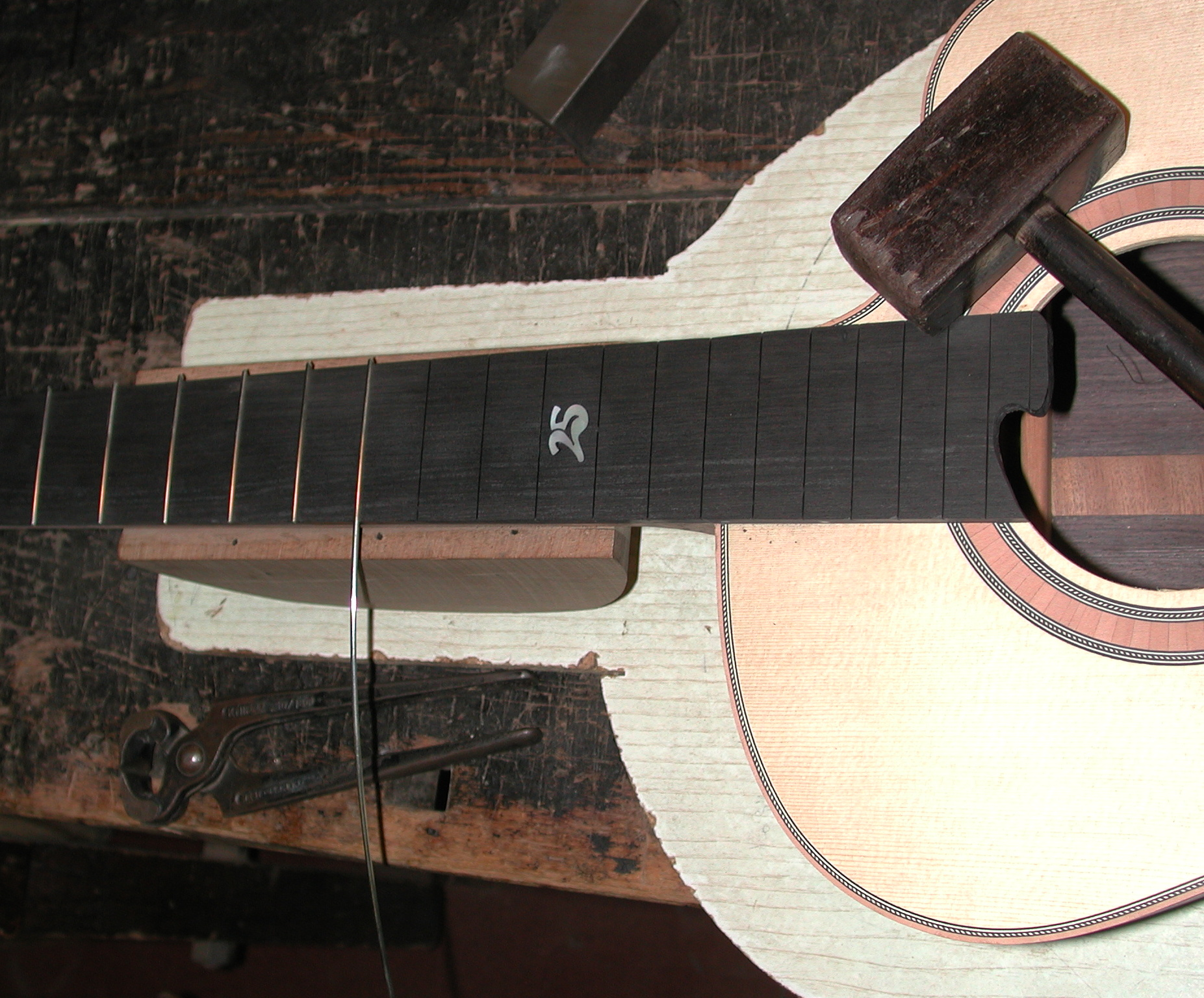 Gitarrenbau Christian Stoll: Hals - Griffbrett Bundieren. Mit dem Holzhammer wird der Bunddraht in die Schlitze geschlagen, eine spezielle Bunddrahtzange bringt die Bünde auf Länge.