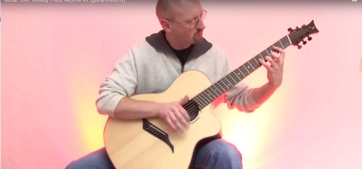Arkadij friedt auf Jumbo Steelstring Gitarre mit Fächerbünden IQ