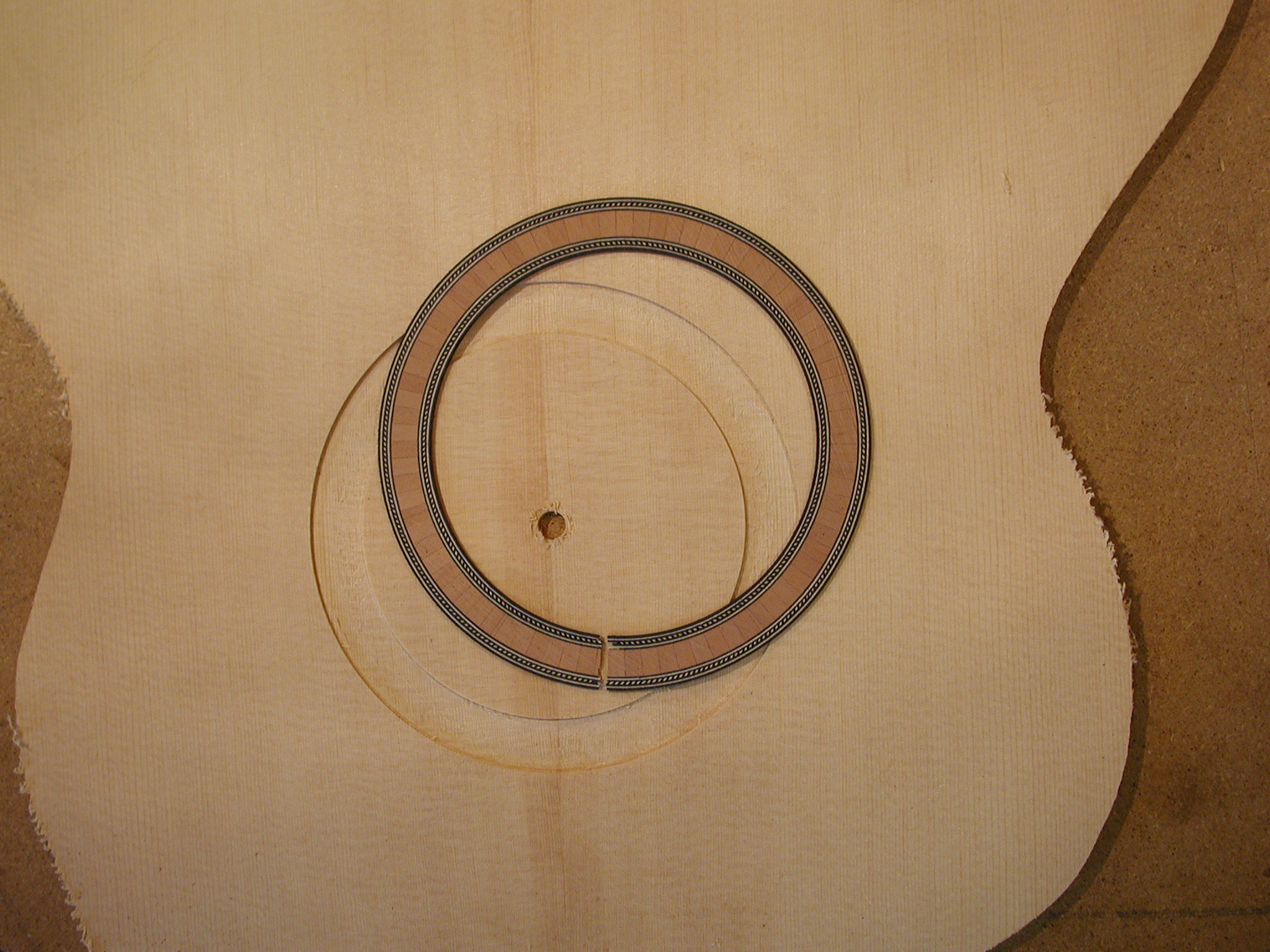 Top: The soundhole rosette is being inserted.