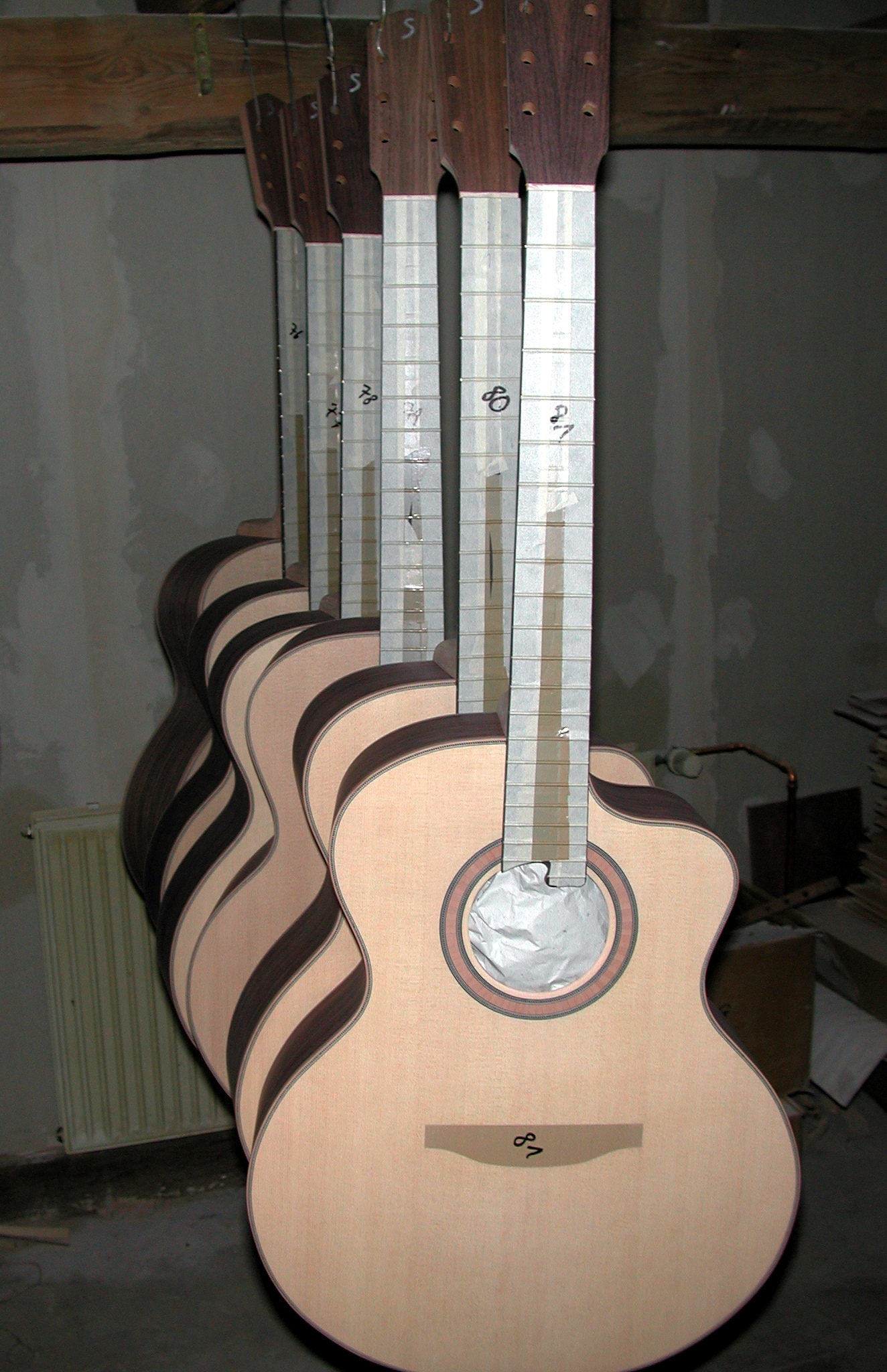 Finishing: The instruments are now ready for finishing. The fretboard and the place for the bridge are masked with tape, the soundhole is clogged with paper, in order to prevent the lacquer from going inside.