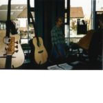 1997 Wieslocher Gitarrentage: Christian Stoll presents his instruments. Left in the foreground two Legendary Acoustic Basses of the third generation. Right in the foreground flyer for the first time offered guitar building workshops